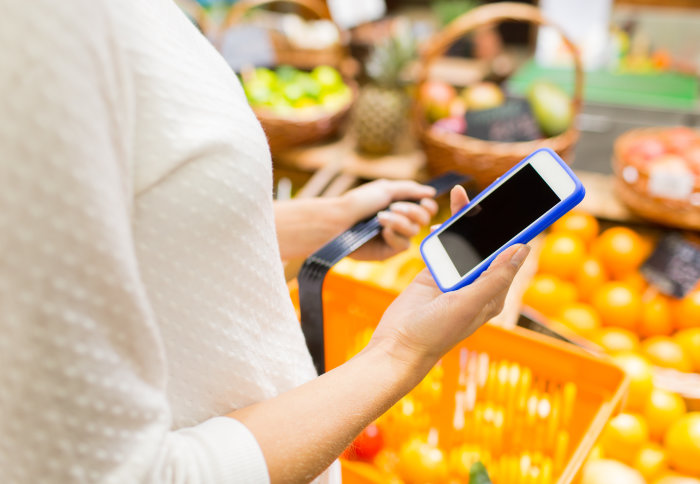 Woman holds smartphone in supermarket in front of fruit and vegetables