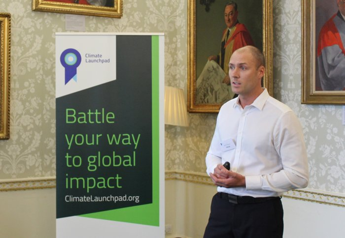 "A man in a white shirt presents in front of a sign reading ""Battle your way to global impact"""