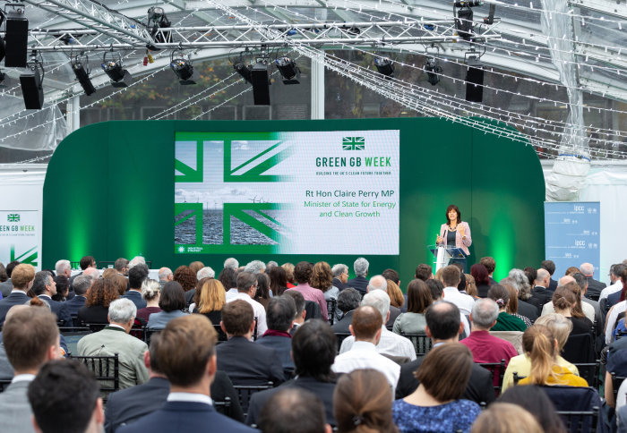 Minister speaks from a green stage in front of an audience of people at the event