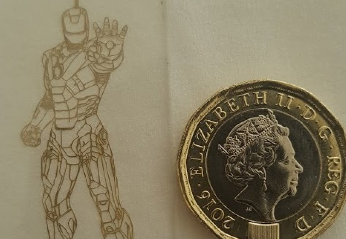 An outline image of Iron man in thin metal next to a pound coin for scale