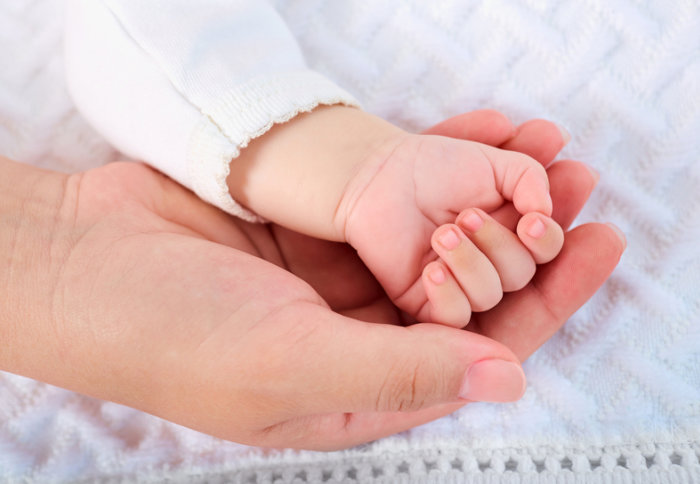 A mother's hand holding a baby's hand