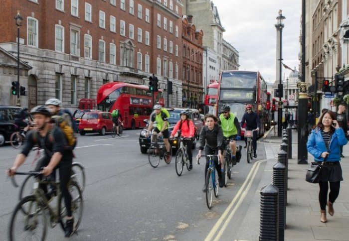 Commuters on London's roads in rush hour - cyclists, car drivers, bus drivers and pedestrians