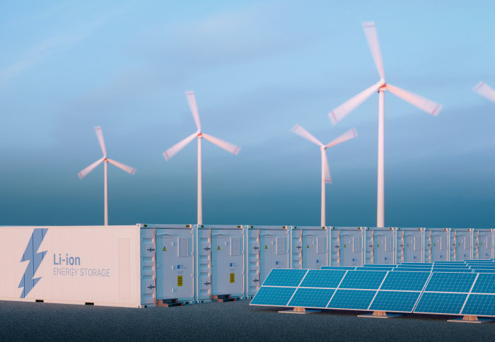 Large containers labelled 'Li-ion energy storage' in front of wind turbines and solar panels