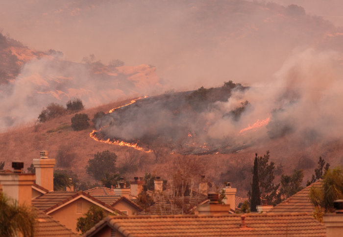 A wildfire spreading on a hill above houses