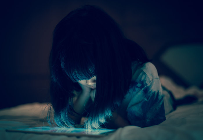 Young girl looking at a tablet in the dark