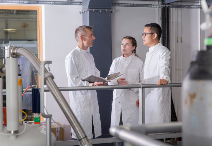 Two students in lab coats talking to a professor in an engineering lab