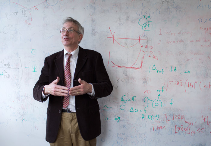 Professor Simon Donaldson stands in front of a white board with mathematics written on it