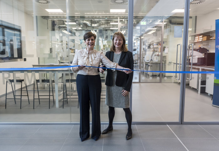 Two women cutting a ribbon in front of a lab