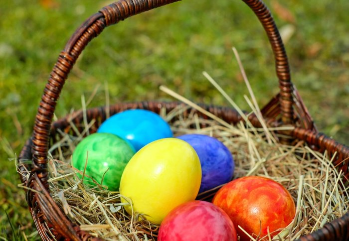 Colourful eggs in basket full of straw