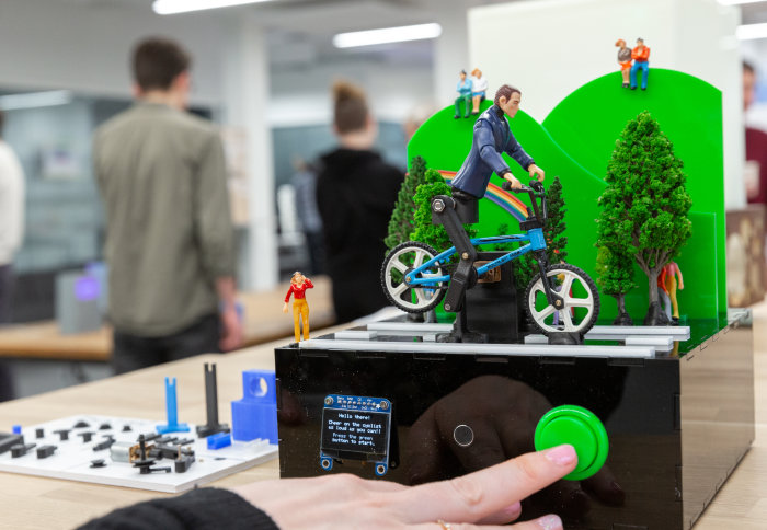 Photo of small robotic man riding bicycle known as Colin the Cyclist