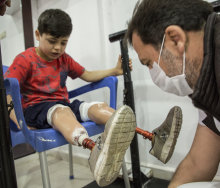 Photo of young boy with two prosthetic legs, being attended to by an adult man.