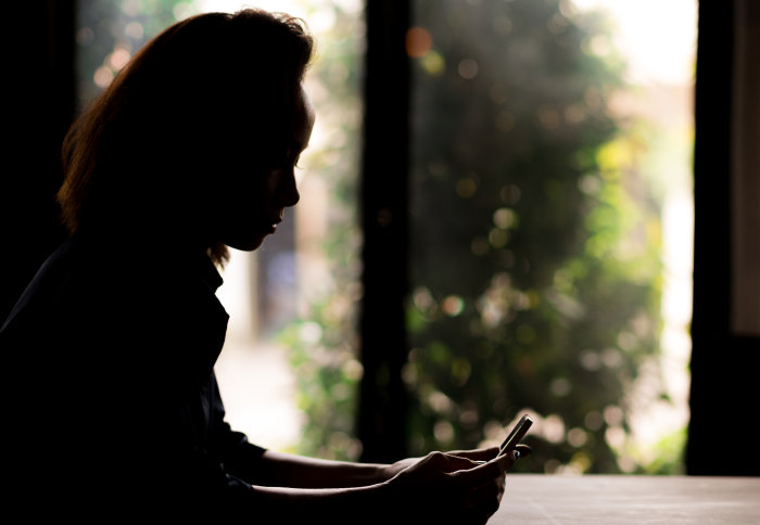 A silhouette of a girl using a mobile phone