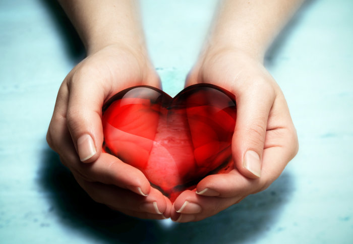 A woman's hands holding a red glass heart