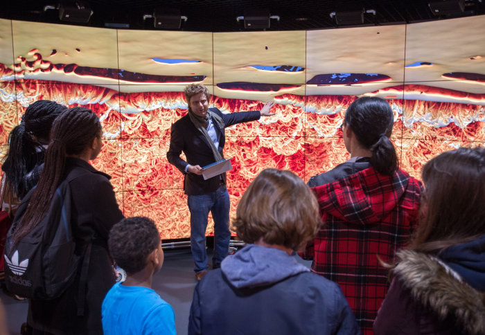 A scientist delivers a talk on Mars, standing in front of a huge digital display