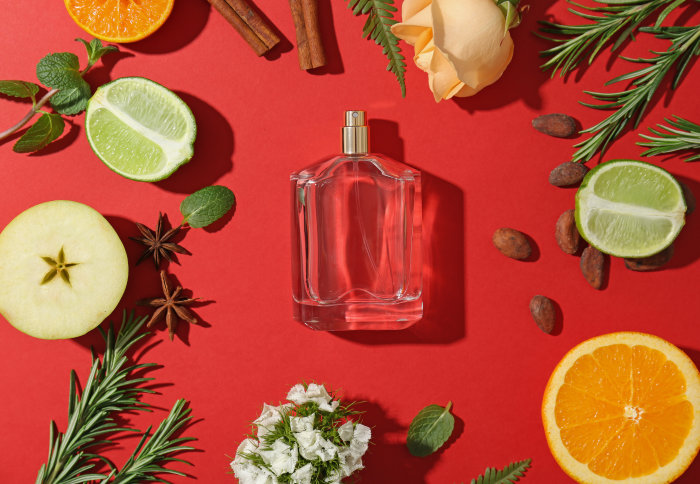 A perfume bottle surrounded by potential ingredients, like orange, rose, lime, vanilla