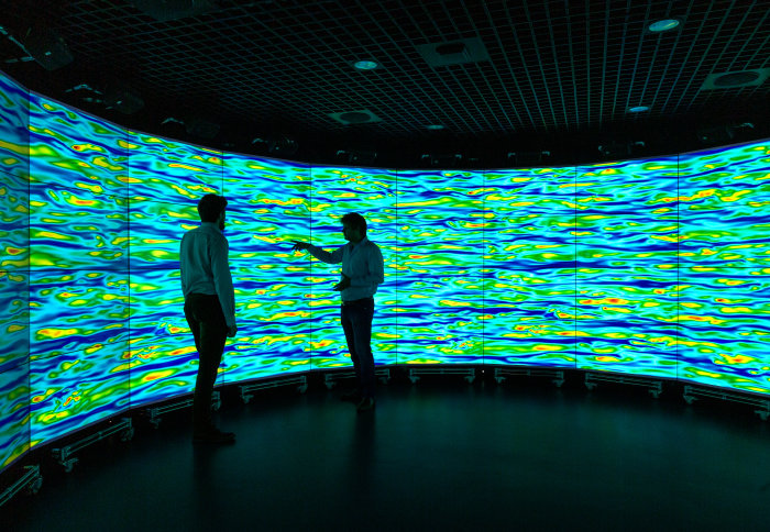 Two people standing in front of wraparound screens showing colourful simulations of turbulent flow
