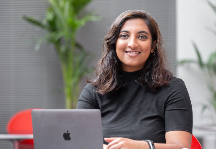 Anita Chandran sits at a laptop