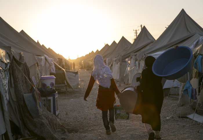 Refugee women carrying supplies in a camp