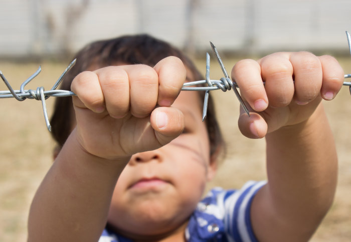 A young child in a minefield holding on to barbed wire