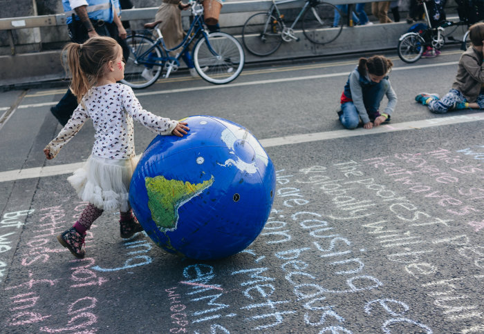 Little girl bounces an inflatable ball printed to look like a globe during climate change protests