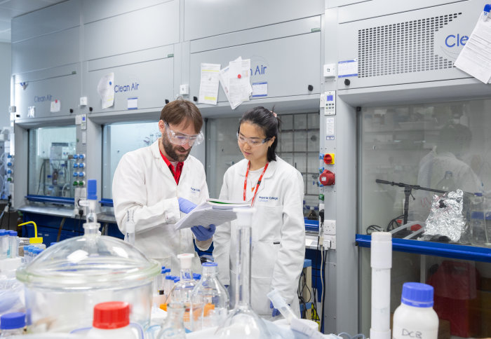 Two people wearing lab coats, standing in a lab.