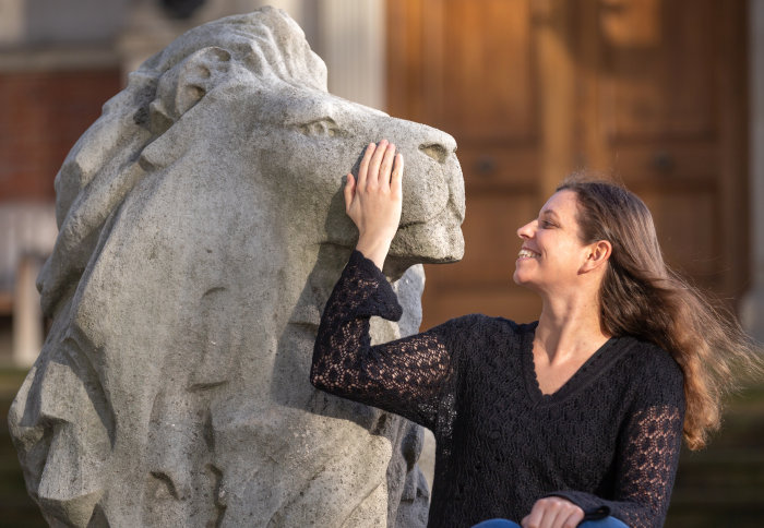 Professor Claudia de Rham with one of the campus' stone lions