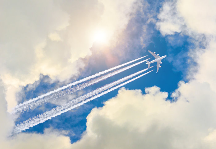 Aeroplane flies through a blue, cloudy sky - contrail trailing behind it.