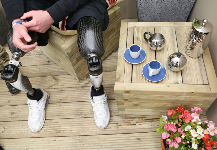 Double leg amputee with prosthetic legs sits by tea set