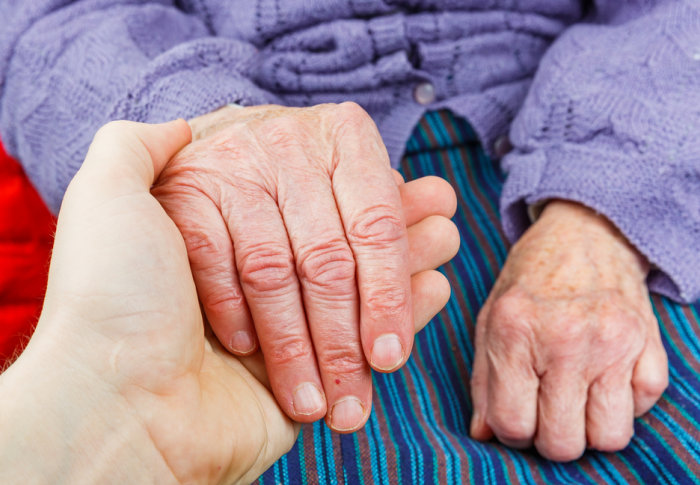 A young person holds the hand of an elderly lady