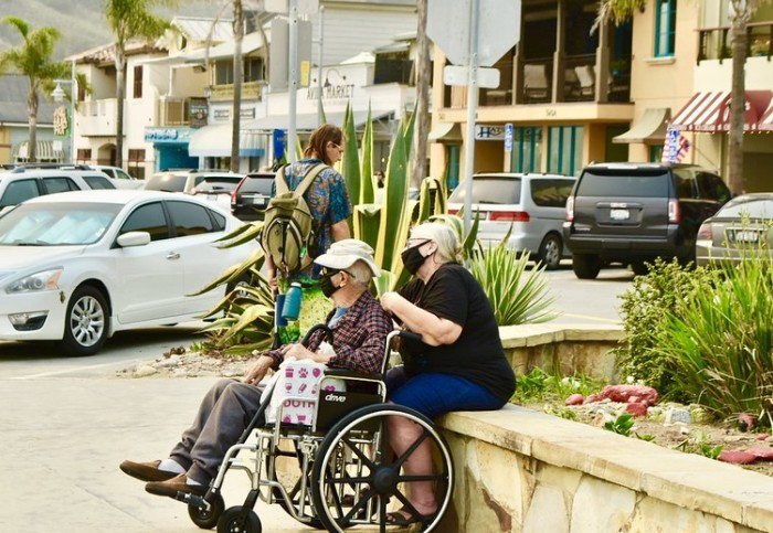 Elderly couple rest in the street wearing face masks to protect them from wildfire smoke in Avila Beach, California (CC-BY-2.0)