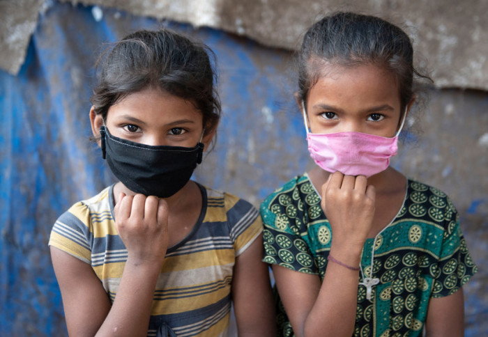 Two young girls wearing facemasks