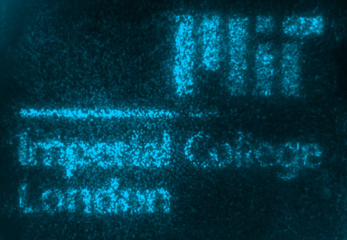 Imperial College London and MIT logos glowing in blue fluorescence caused by the engineered living materials (ELMs)