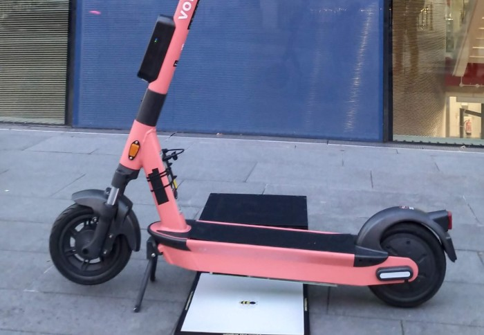 A Voi scooter with an integrated wireless charging receiver, over a wireless charging pad that can be embedded in the pavement