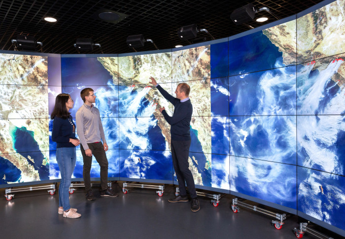 Professor Apostolos Voulgarakis standing in the Data Observatory, discussing with younger researchers. On the screens is displayed a satellite image of wildfires in California.