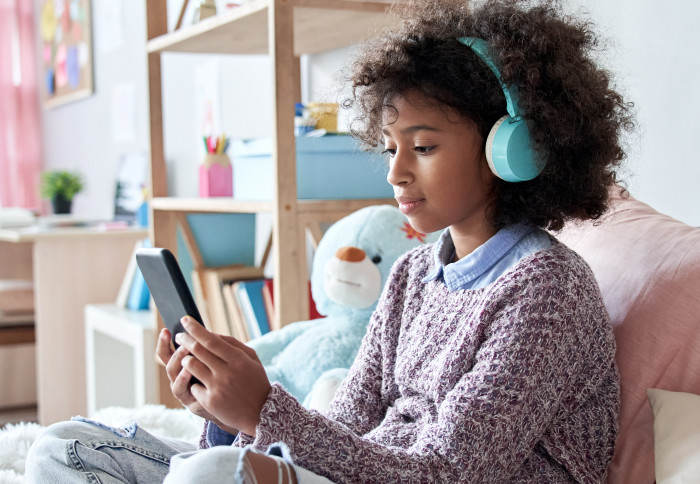 African-American girl wearing headphones holding phone sitting on bed.