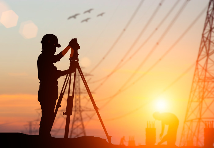 A silhouetted civil engineer surveys the land next to some high voltage transmission lines