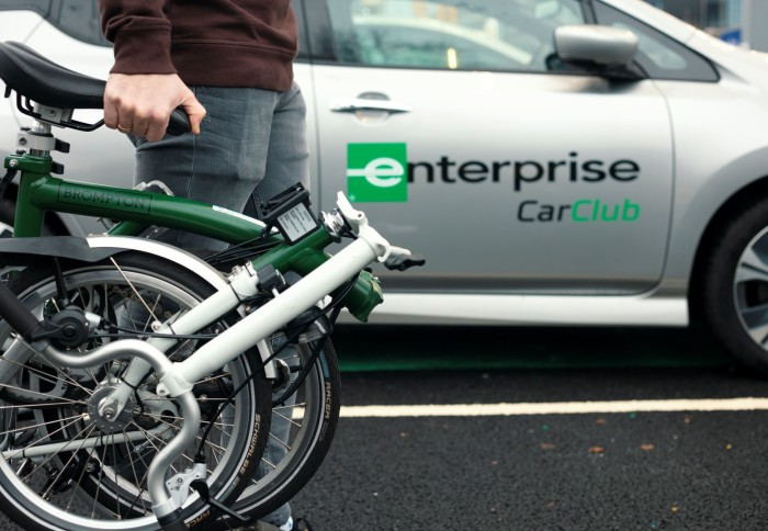 Person carrying a folding bike with a car in the background