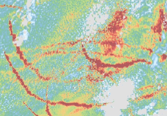 False-colour satellite image showing lines of red that corresponds to ship tracks