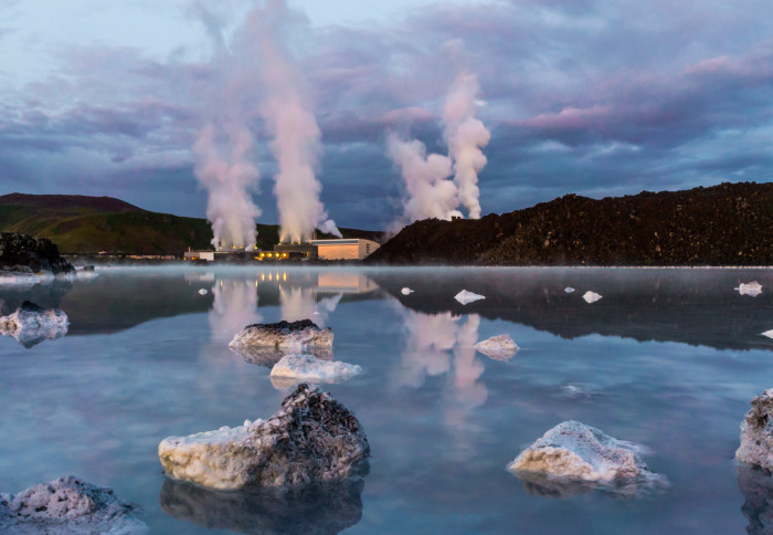 Photo of Svartsengi Geothermal Power Plant in Iceland steaming massively with reflection in a blue water of geothermal pool after the sunset and dramatic blue violet sky with thick clouds