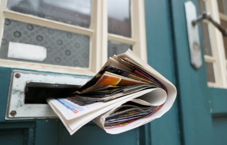 A newspaper going through a letterbox