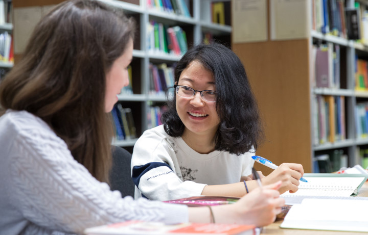 Two students smiling together in Imperial Library