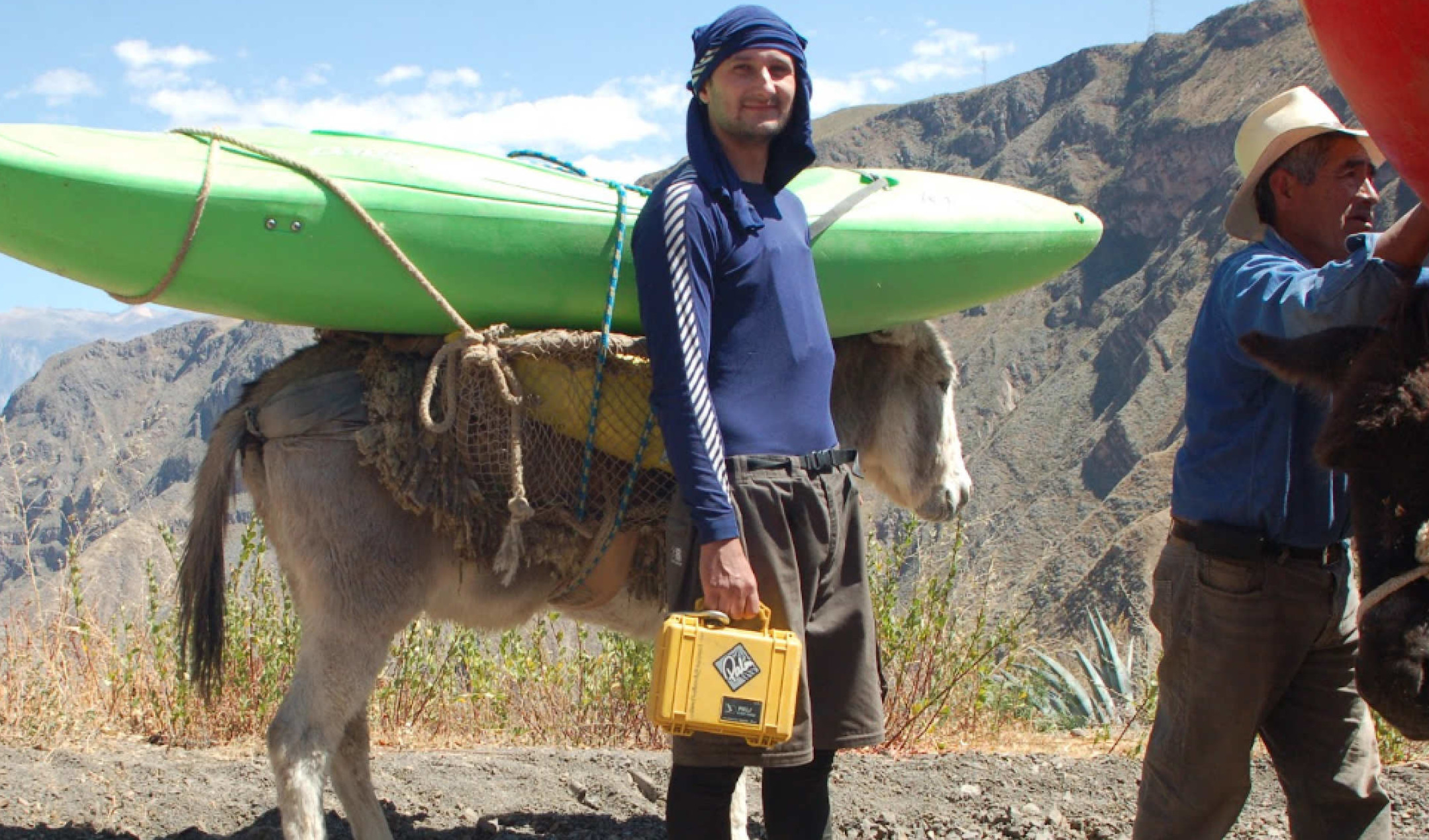 student with kayak on mule in background