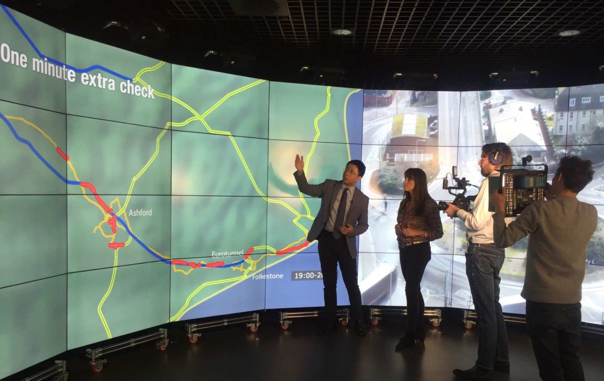 Photo of Dr Han showing BBC journalist through his findings on the Data Observatory while being filmed