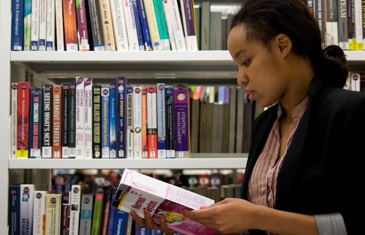 woman stood in front of book shelves reading from a book