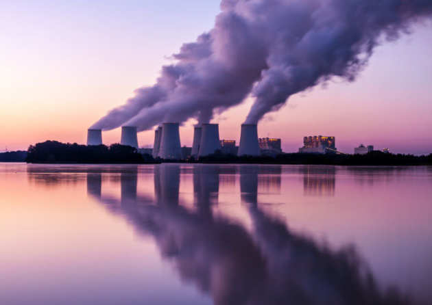 power stations billowing smoke with reflection in the lake in front