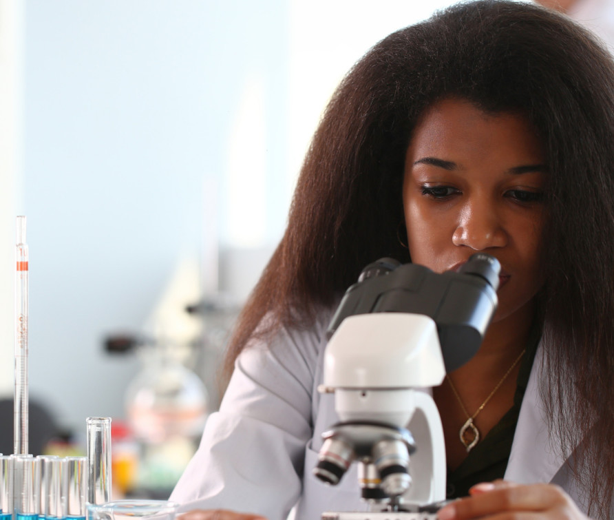 A black woman in a lab looking into a microscope