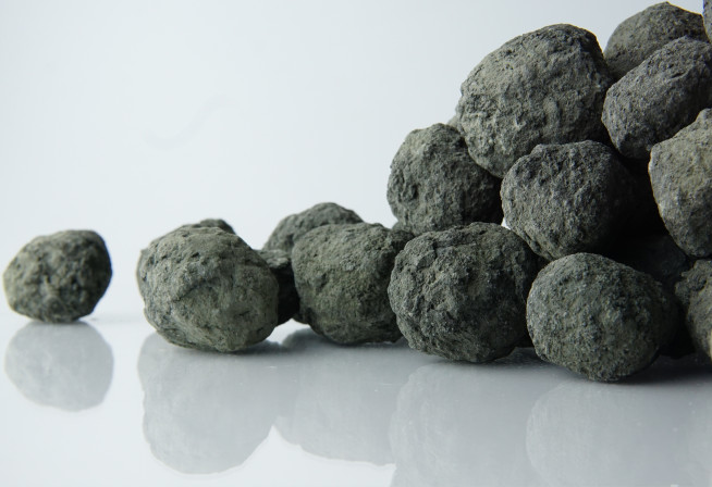 Balls of grey cement clinker on white background