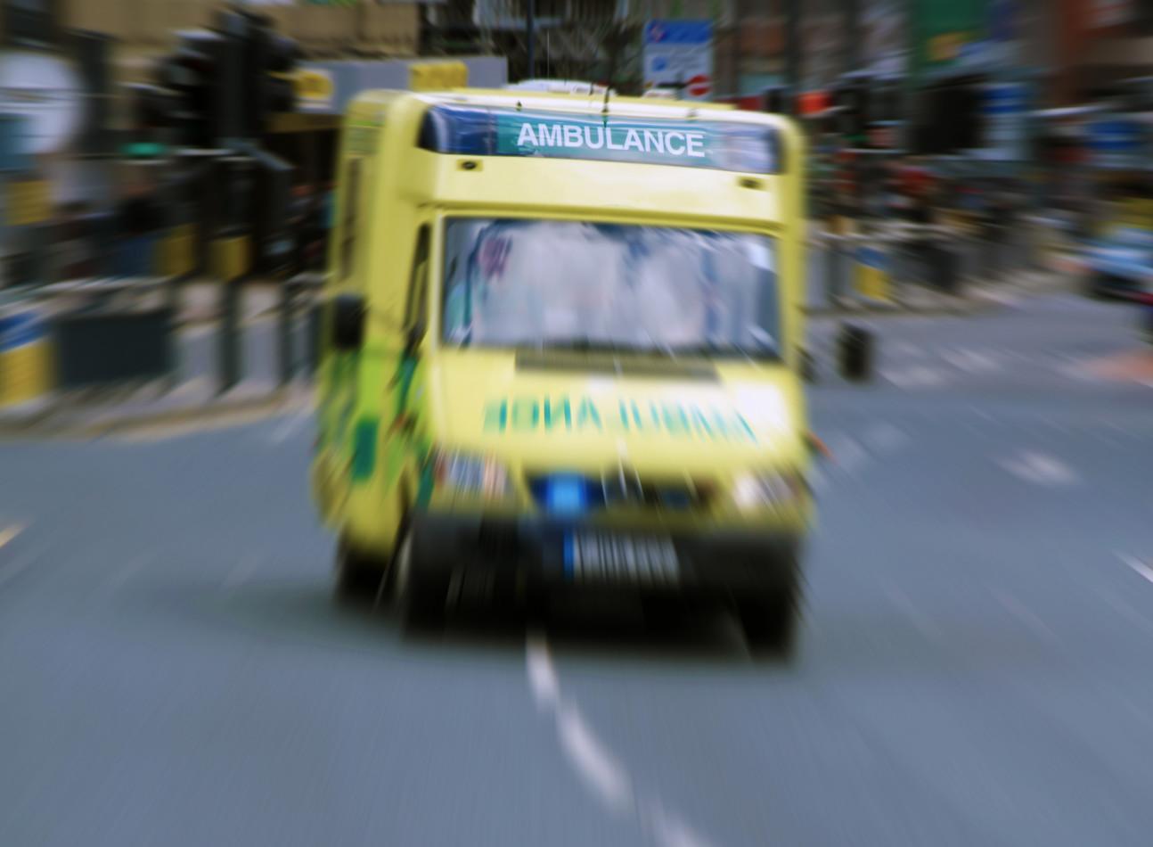 An ambulance speeding through a busy street