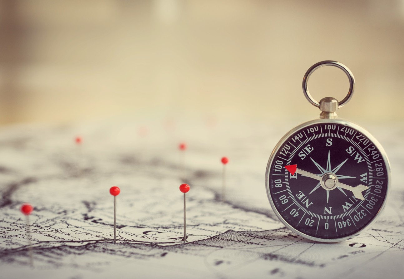 An image of a compass and map with pins in it