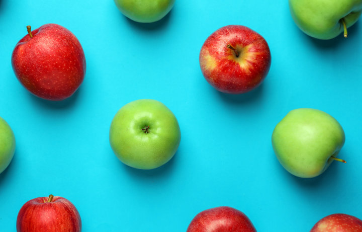 Similiar apples on color background - a suggestive image to depict plagiarism